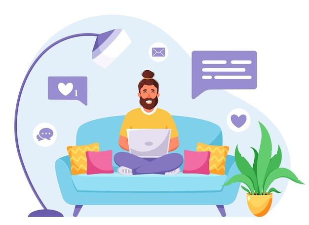 소파에 앉아 노트북에서 일하는 남자 프리랜서 홈 오피스