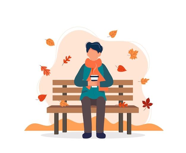 コーヒーを飲みながら秋のベンチに座っている男。