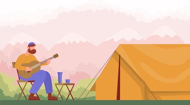 캠핑 의자에 앉아 야외 하이킹을 위한 텐트 개념 근처에서 기타를 연주하는 남자