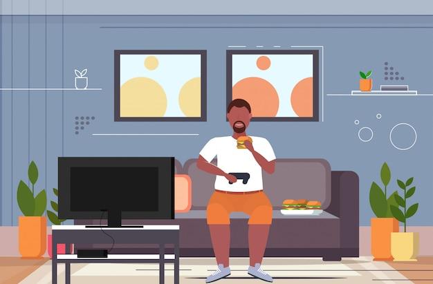 Человек сидя на диване ест гамбургер с помощью джойстика игровой коврик избыточный вес парень курсирует видеоигры на тв концепция нездоровый образ жизни интерьер гостиной горизонтальный полная длина