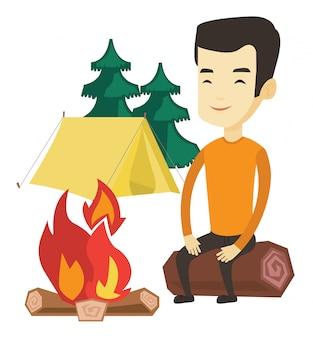 キャンプのキャンプファイヤーの近くの丸太に座っている男。