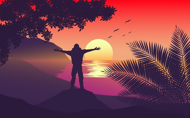 Man standing on cilff with arms streching in sunset