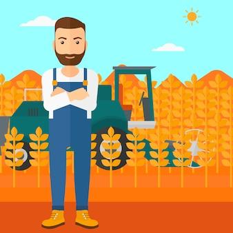 Человек стоя с зернокомбайном на предпосылке.