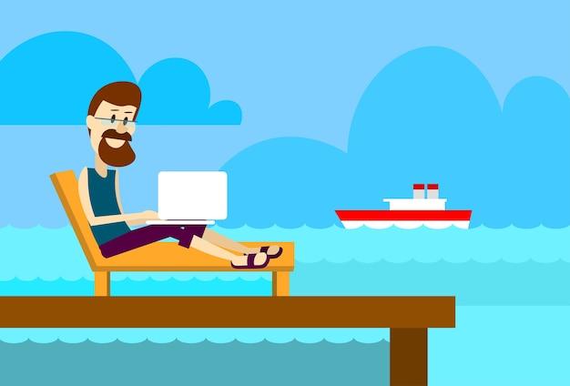 Man on sunbed using laptop