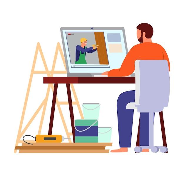 ツールとペンキ缶に囲まれた男がノートパソコンで自分でやるビルダーのビデオブログを見てください。
