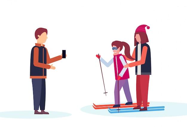 Man taking photo to skiers couple