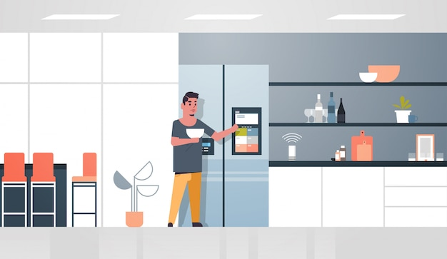 Man touching refrigerator screen with smart speaker