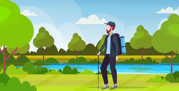 Человек турист турист с рюкзаком держа палку треккинг пеший туризм концепция путешественник на поход красивая река пейзаж фон полная длина горизонтальный плоский