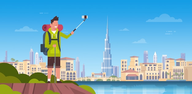 Man tourist with backpack taking selfie photo over beautiful dubai city background