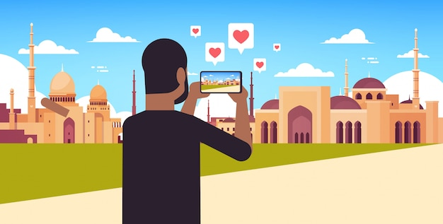 Man traveler photographing nabawi mosque building on smartphone