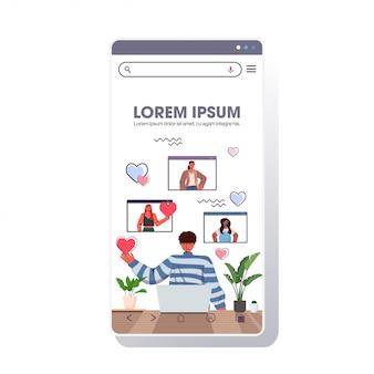 ラップトップを使用している人は、webブラウザーのウィンドウのオンラインデートアプリの社会的関係のコミュニケーションの概念のスマートフォンの画面の肖像画のコピースペースイラストで混血の女性とチャットします。