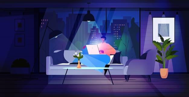 Человек, использующий ноутбук в темной ночной гостиной, концепция онлайн-общения в сети социальных сетей