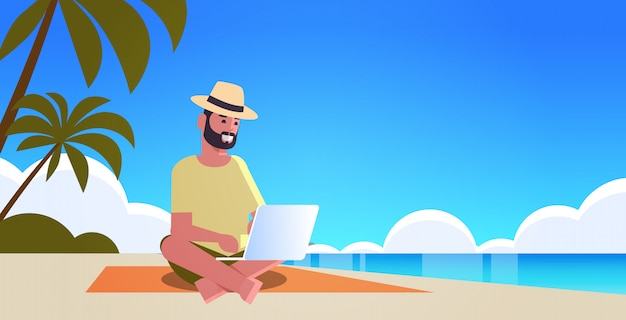 Man using laptop on tropical sea beach summer vacation online communication blogging concept seascape background full length horizontal