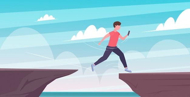 Man using smartphone jumping over cliff gap risk danger digital addiction concept  full length horizontal
