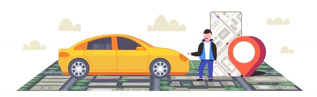 スマートフォンを使用して建物と通りのカーシェアリングの概念都市景観トップアングルビュー全長水平の市内地図上の位置gps位置でタクシーモバイルナビゲーションアプリを注文する男