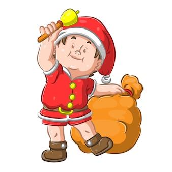 Мужчина в рождественском костюме держит колокольчик и мешок с подарками