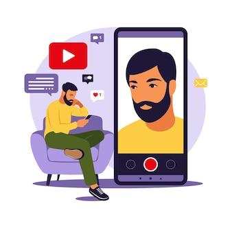 電話でソファに座ってスマートフォンでビデオを録画する男のビデオブロガー。