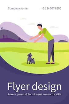 屋外で犬と一緒に歩く男。地面の平らなチラシテンプレートから子犬を選ぶために手を伸ばす男
