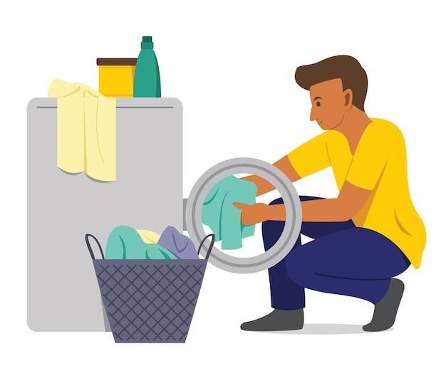 남자는 세탁기로 옷을 씻는다.
