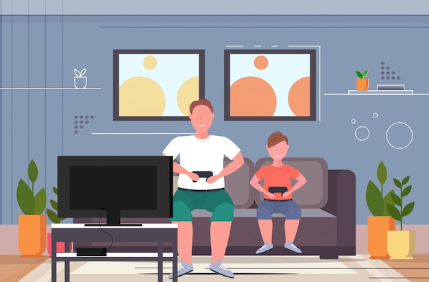Man with child sitting on couch using joystick overweight father and son plying video games on tv obesity unhealthy lifestyle concept modern living room interior horizontal full length