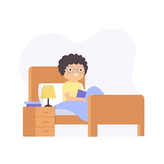 Man with curly hair reading a book in bed