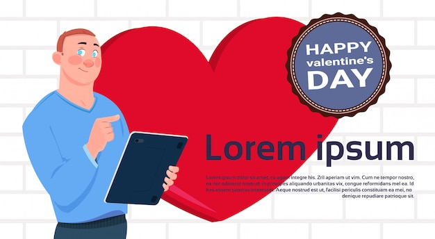 Man with digital tablet over heart shape background and happy valentines day label banner with copy space