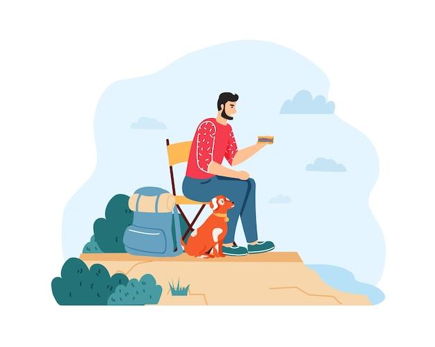 Человек с собакой в поход и летнее путешествие. парень сидит на стуле и ест бутерброд возле рюкзака на скале с домашним животным.