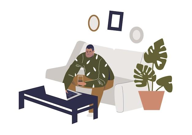 Человек с ноутбуком, сидя на диване у себя дома