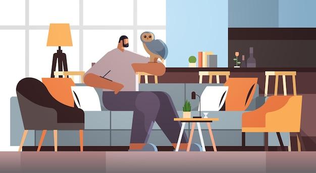 Man with owl guy taking care of pet animal bird living room interior horizontal