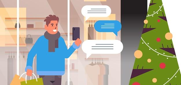 Человек с сумками, используя мобильное приложение в чате на смартфоне, социальная сеть, чат, пузырь, общение, рождественские праздники, концепция, портрет, горизонтальная векторная иллюстрация