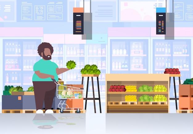野菜や果物の男スーパーマーケットの顧客の概念の食料品店のインテリア水平完全な長さを選択するショッピングトロリーカートを持つ男