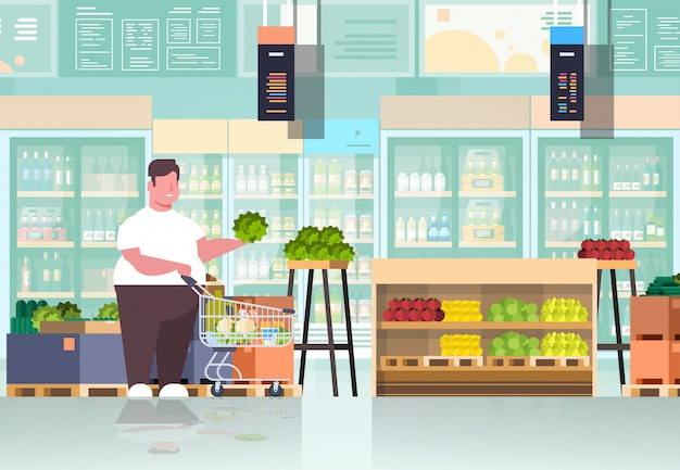 野菜や果物の男スーパーマーケットの顧客を選択するショッピングトロリーカートを持つ男
