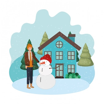 Man with snowman and house in winter