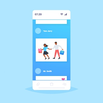 Man woman carrying shopping bags couple having fun walking together holiday sales shop retail consumer concept smartphone screen mobile application  full length