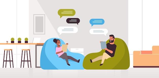 男性女性チャットメッセージングミックスレースカップルタブレットソーシャルネットワークチャットバブル通信でモバイルアプリを使用して豆袋に座っています。