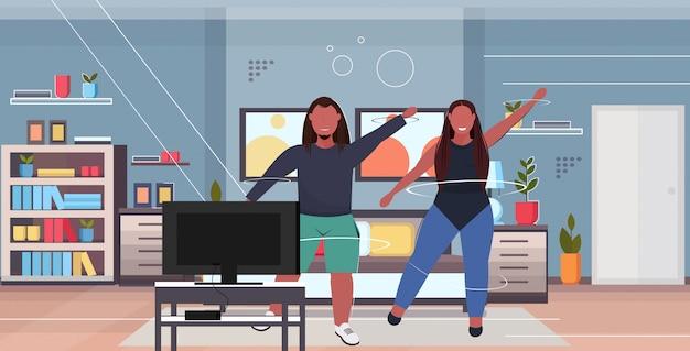 Мужчина женщина занимается аэробикой во время телешоу перед телевизором парень тренировка тренировка фитнес потеря веса концепция современная гостиная интерьер полная длина горизонтальный