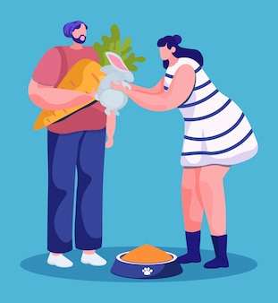 Man and woman feeding domestic pet with carrot. isolated couple of hipsters giving vegetable to bunny
