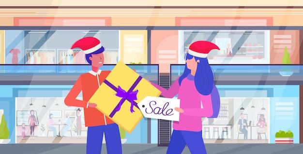 季節の販売コンセプトモダンなショッピングモールのインテリアの肖像画の最後のギフトボックス顧客カップルのために戦うサンタ帽子の男性女性買い物客