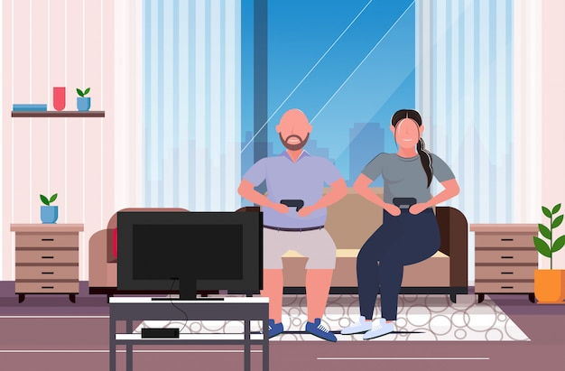 Man woman sitting on couch using joystick game pad overweight couple plying video games on tv obesity unhealthy lifestyle concept modern living room interior horizontal full length