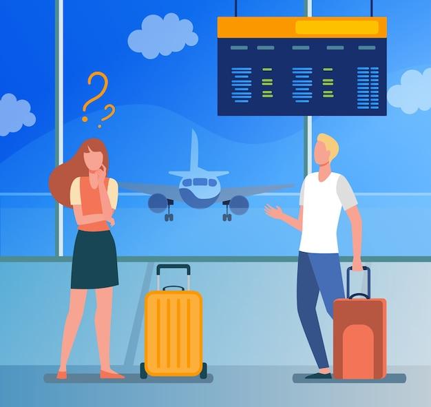 Uomo e donna in piedi in aeroporto e scegliendo la direzione.