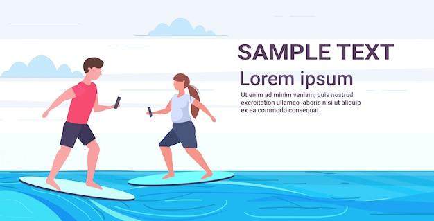 Мужчина женщина серферов холдинг мобильных телефонов серфинг на волне пара с помощью смартфонов онлайн мобильное приложение концепция цифровой наркомании полная длина горизонтальный копией пространства