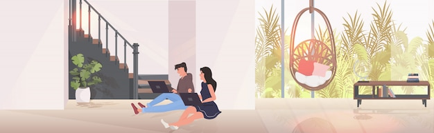 Man woman using laptops couple sitting on floor spending time together modern living room interior