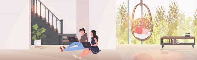 Мужчина женщина, используя ноутбуки пара, сидя на полу, проводить время вместе интерьер современной гостиной
