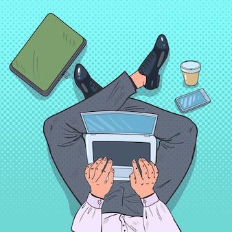 Человек, работающий с ноутбуком на полу