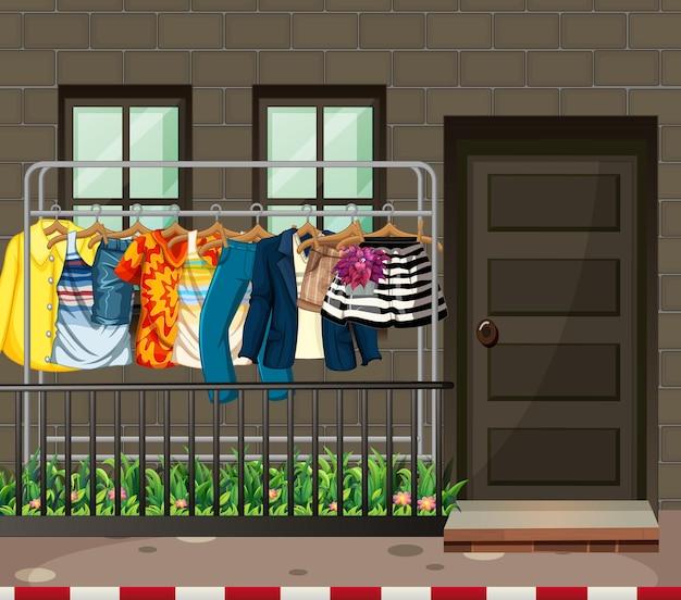 家の前のハンガーにたくさんの洋服がぶら下がっています