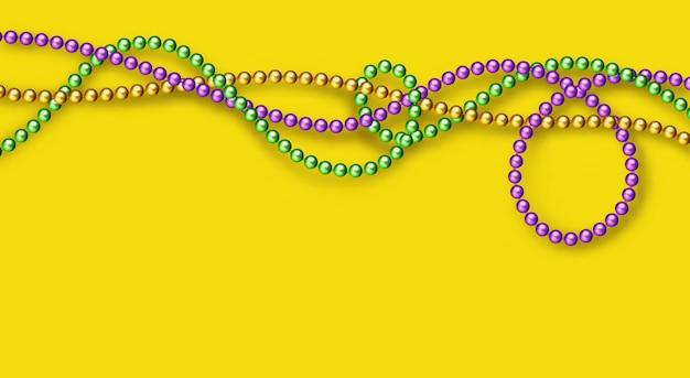 Бусы mardi gras традиционных цветов на желтом фоне. декоративные глянцевые реалистичные элементы для дизайна марди гра. бусы изолированные на прозрачном фоне.