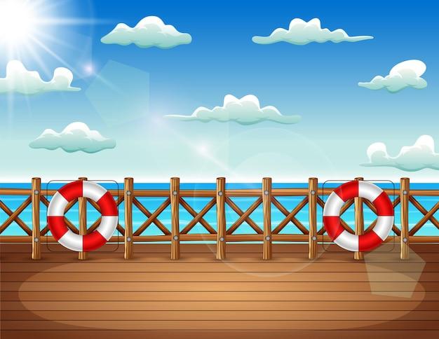 海景と救命浮輪のある海の木製の桟橋