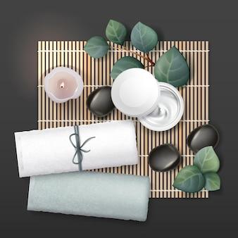 Состав массажных принадлежностей. крем, свеча, камни, полотенца, растения.