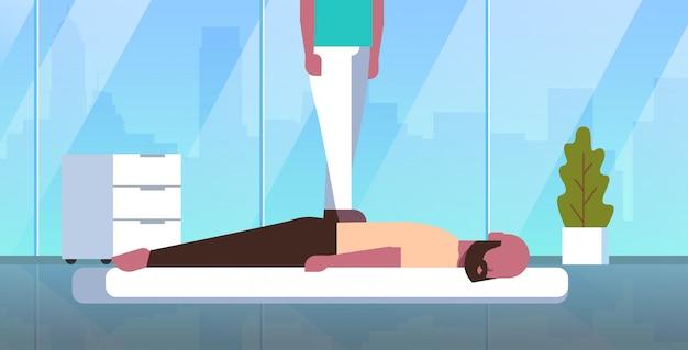 Массажистка стоять на спине пациента делать лечебный парень расслабляющий лежать на столе человек массаж массажист салон салон мануальная терапия концепция современный горизонтальный кабинет кабинет
