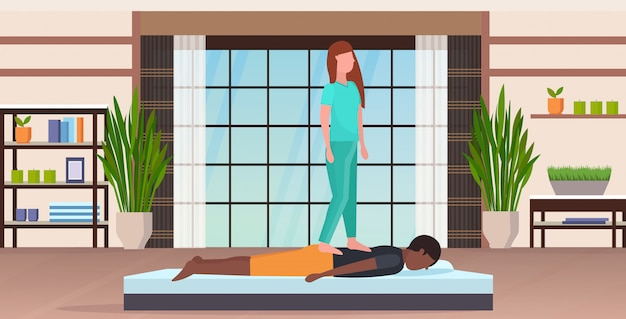 Masseuse in uniform standing on patient's back doing healing treatment  guy having massage manual therapy concept modern spa salon studio interior full length horizontal
